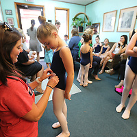 Kellie Mathis pins her daughters, Morgan, 8, audition number on her hip before Sunday's Nutcracker audition at Tupelo Ballet.