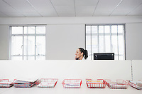 Female office worker using telephone smiling in office cubicle behind trays with documents