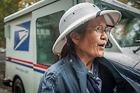 "Letter carrier Connie Gumataotao delivers mail on a rainy day in Calistoga.  ""I've been delivering mail in Calistoga for 19 years...I know where everyone lives."""