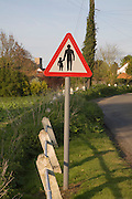 Red triangular Highway Code child and adult road sign warning of no pavement ahead, Suffolk, UK