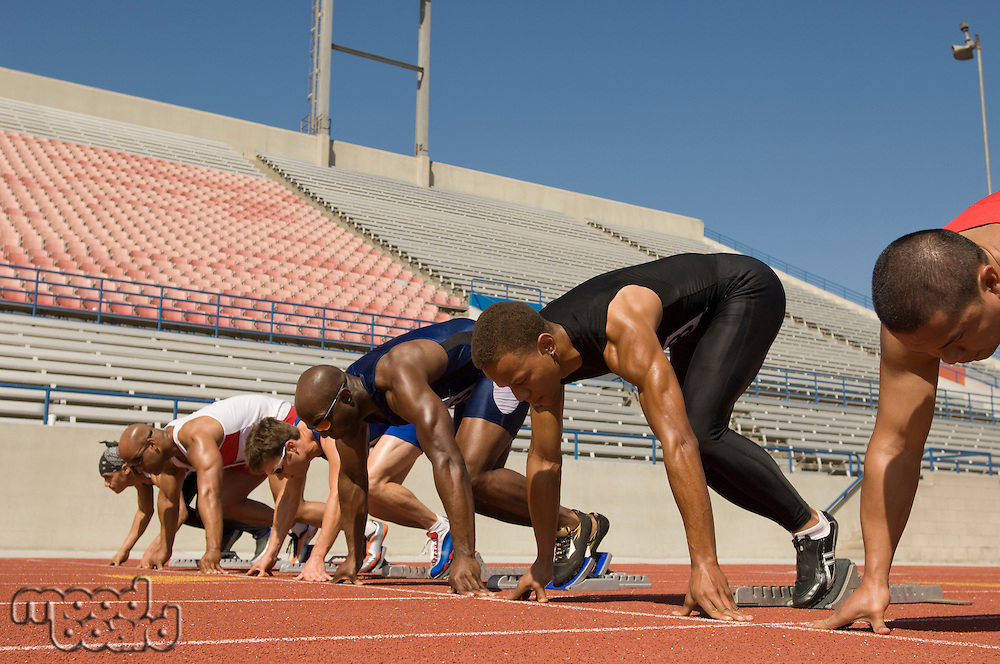 Runners waiting in starting blocks on track