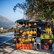 A woman sells clementines and olive oil on the side of the road near the Adriatic Coast in Croatia.