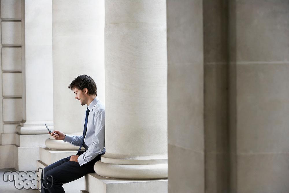 Businessman outside building sitting on pillar sending text message