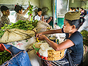 26 OCTOBER 2015 - YANGON, MYANMAR:  A vendor makes noodles dishes for customers on the Yangon Circular Train. The Yangon Circular Railway is the local commuter rail network that serves the Yangon metropolitan area. Operated by Myanmar Railways, the 45.9-kilometre (28.5 mi) 39-station loop system connects satellite towns and suburban areas to the city. The railway has about 200 coaches, runs 20 times daily and sells 100,000 to 150,000 tickets daily. The loop, which takes about three hours to complete, is a popular for tourists to see a cross section of life in Yangon. The trains run from 3:45 am to 10:15 pm daily. The cost of a ticket for a distance of 15 miles is ten kyats (~nine US cents), and for over 15 miles is twenty kyats (~18 US cents).     PHOTO BY JACK KURTZ