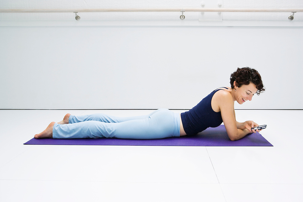 A young woman resting on a yoga mat in a white room using her cell phone.