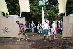 Image ©Licensed to i-Images Picture Agency . 20/07/2014 . Henham Park , Suffolk , United Kingdom . Wellies out - people tread carefully through mud at the camp site . The Latitude Festival of music and arts . Picture by Joel Goodman/i-Images