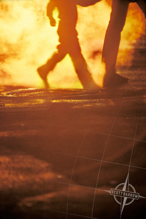 Parent and child crossing a city street with backlit steam at sunset.