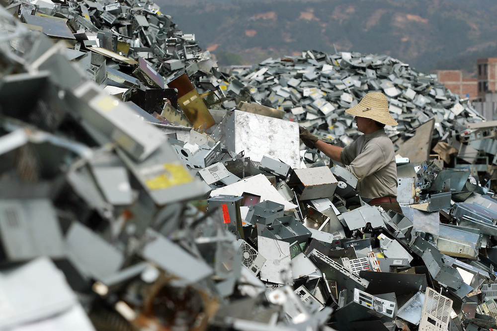 A junk yard worker sorts electronic trash and old pc bodies at a dump in Guiyu, China March 8, 2005. For years, developed countries have been exporting tons of electronic waste to China for inexpensive, labor-intensive recycling and disposal. Since 2000, it's been illegal to import electronic waste into China for this kind of environmentally unsound recycling. But tons of debris are smuggled in with legitimate imports, corruption is common among local officials, and China's appetite for scrap is so enormous that the shipments just keep on coming...