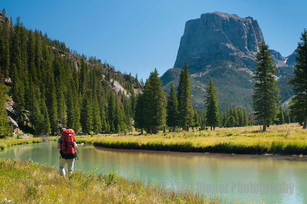A young woman hikes along the upper Green River in the Wind River Mountains, Wyoming.