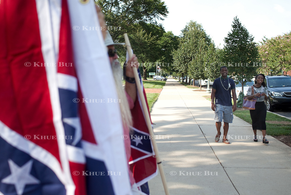 Charles Marshall, 24, and Zaire Graves, 22, both of Richmond, walk past members of the Virginia Flaggers protesting with Confederate flags outside the Virginia Museum of Fine Arts Tuesday, June 30, 2015, in Richmond, VA.  <br /> <br /> Photos by Khue Bui