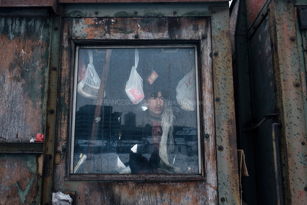 An Afghan migrant looks outside an abandoned wagon, the place where he is living alongside other five Afghan friends. They are surviving a subzero winter with no electricity, no heating, or water.