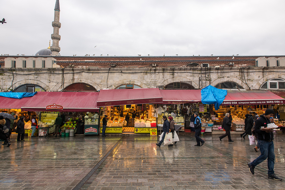 Shoppers walk the rainy streets to browse the outdoor market stalls that have spilled out from the inside of  Istanbul Spice bazaar in Turkey