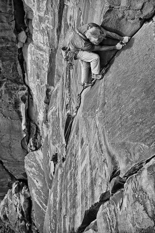 "Jay Smith climbing his route ""Voodoo Child,"" Grade V, 5.11+ on Parriott Mesa, S. Utah"