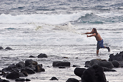 An unidentified fisherman throws his net while standing on the remains of an ancient breakwater known as Paokamenehune or menehune breakwater built by early Hawaiians, near Kahaluu Beach Park in Keauhou on the Big Island of Hawaii.