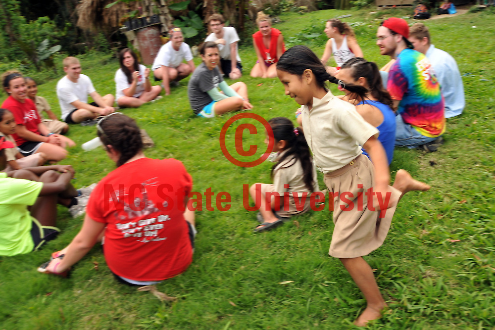 A neighborhood girl chases of Team Belize as they play a rousing game of Duck, Duck, Goose after lunch.