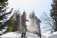 Couple playing in snow on hill