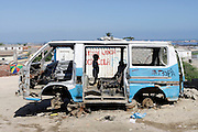 A child plays in a damaged mini bus taxi in a shanty town outside of Lobito. Benguela Province, Angola. Africa. .Pictures © Z & D Lightfoot..www.lightfootphoto.co.uk