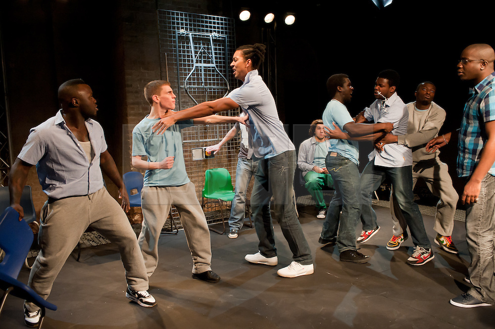 """© Copyright licensed to London News Pictures. 12/11/2010. """"Inside"""" by Philip Osment, presented by Playing Out at the Roundhouse, Camden, London. Based on the real experiences of young fathers in prison, the play deals with big questions surrounding relationships, both with their own fathers and with their children. In this scene, a fight breaks out. The cast: Jim Pope, Andre Skeete, Ayo Bodunrin, Kyle Thorne, Michael Amaning, Darren Douglas, Segun Olaiya, Jacob James Beswick, Tarkan Cetinkaya."""
