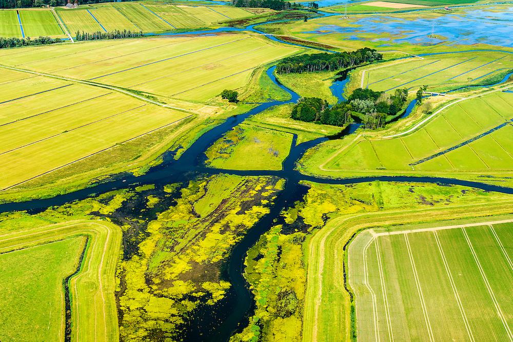 Nederland, Noord-Brabant, Werkendam, 23-08-2016; Ruimte voor de Rivier project Ontpoldering Noordwaard. Foto richting rivier de Nieuwe Merwede. De bandijk (winterdijk) is voorzien van doorlaten annex brug, boerderijen zijn op terpen gebouwd. De dijken aan de rivierzijde zijn gedeeltelijk afgegraven waardoor rivier de Nieuwe Merwede bij hoogwater via de Noordwaard en de Biesbosch sneller naar zee stromen. Gevolg van de ingrepen is dat de waterstand verder stroomopwaarts zal dalen. Ook de getijden keren terug in het gebied.<br /> National Project Ruimte voor de Rivier (Room for the River) By lowering and moving the dike of the Noordwaard polder the area will become subject to controlled inundation and function as a dedicated water detention district. Houses and farmhouses havbeen demolished and rebuild  on new dwelling mounds.<br /> luchtfoto (toeslag op standard tarieven);<br /> aerial photo (additional fee required);<br /> copyright foto/photo Siebe Swart