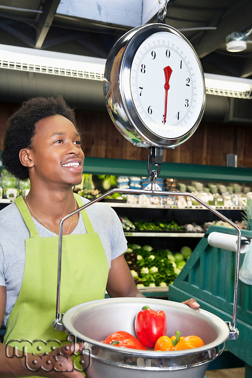 Male African American store clerk weighing bell peppers on scale