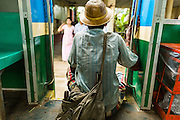 15 JUNE 2013 - YANGON, MYANMAR:   A man sits in the doorway of the Yangon Circular Train. The Yangon Circular Railway is the local commuter rail network that serves the Yangon metropolitan area. Operated by Myanmar Railways, the 45.9-kilometre (28.5 mi) 39-station loop system connects satellite towns and suburban areas to the city. The railway has about 200 coaches, runs 20 times and sells 100,000 to 150,000 tickets daily. The loop, which takes about three hours to complete, is a popular for tourists to see a cross section of life in Yangon. The trains from 3:45 am to 10:15 pm daily. The cost of a ticket for a distance of 15 miles is ten kyats (~nine US cents), and that for over 15 miles is twenty kyats (~18 US cents). Foreigners pay 1 USD (Kyat not accepted), regardless of the length of the journey.     PHOTO BY JACK KURTZ