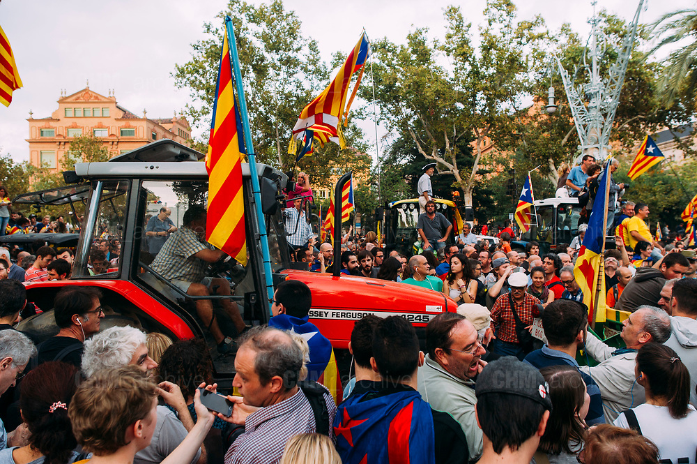 Supporters of Catalan independence wave Catalan flags as they drive with tractors through the Arc de Triomf (Triumphal Arch) in Barcelona on October 10, 2017. Spain's worst political crisis in a generation will come to a head as Catalonia's leader could declare independence from Madrid in a move likely to send shockwaves through Europe.  10, 2017 in Barcelona, Spain. Christian Mantuano / OneShot