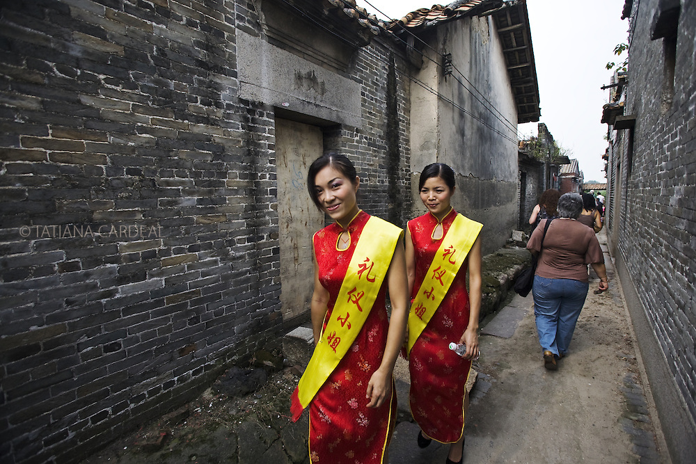 Young women dressed with traditional colors for celebration, crossing through the gray walls of Cha Tang Village, at Guangzhou periphery.