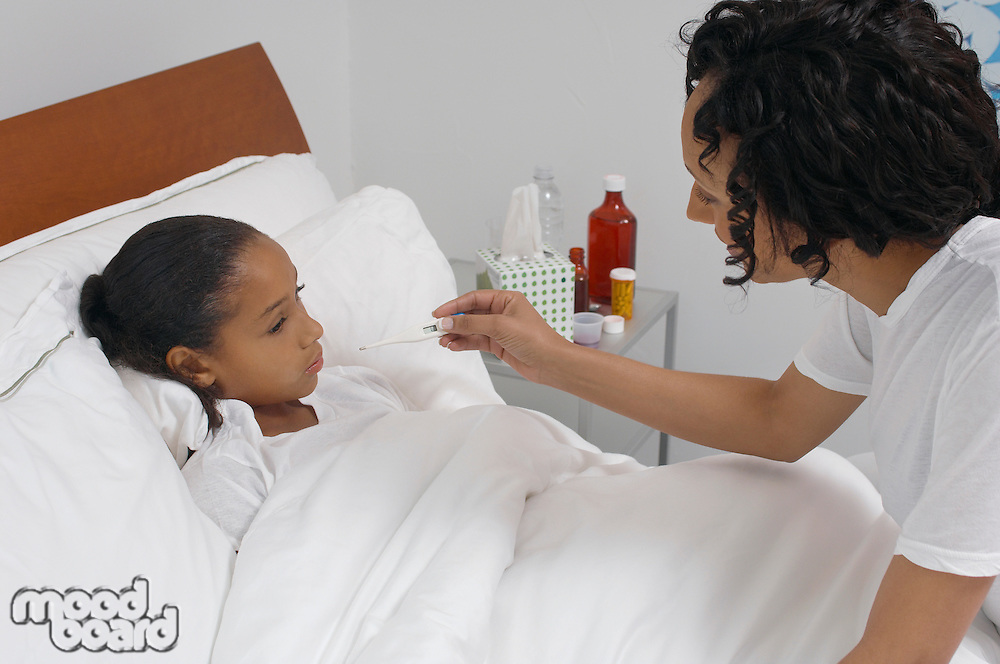 Nurse taking temperature of girl (7-9) lying in bed