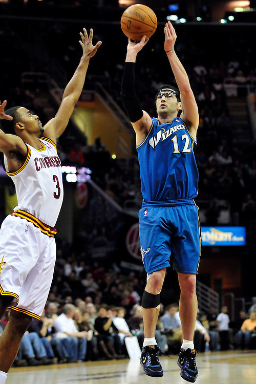 Feb. 13, 2011; Cleveland, OH, USA; Washington Wizards guard Kirk Hinrich (12) shoots over Cleveland Cavaliers point guard Ramon Sessions (3) during the second quarter at Quicken Loans Arena. Mandatory Credit: Jason Miller-US PRESSWIRE
