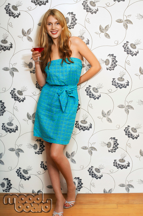 Woman standing by floral print wall Drinking Martini portrait