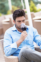 Young man drinking red wine at outdoor restaurant