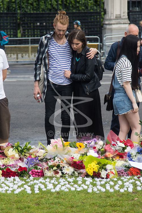 Parliament Square, Westminster, London, June 17th 2016. Following the murder of Jo Cox MP friends and members of the public lay flowers, light candles and leave notes of condolence and love in Parliament Square, opposite the House of Commons. PICTURED: A couple, the woman tearful, comfort each other as they look at the tributes.