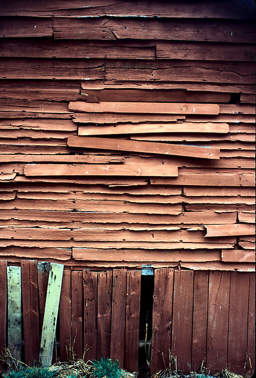 Siding detail of a derelict wooden barn in rural Virginia.  Its planks make rough horizontal parallels.  Unused, it still stands like an old old man.