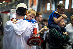 © Licensed to London News Pictures . 30/07/2017 . Manchester , UK . Weary-looking Captain America Branden Fraine (four, from Rochdale) is carried through crowds on his father's shoulder . Cosplayers, families and guests at Comic Con at the Manchester Central Convention Centre . Photo credit : Joel Goodman/LNP