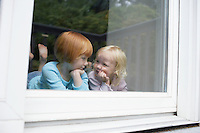 Sisters (3-6) indors in front of window
