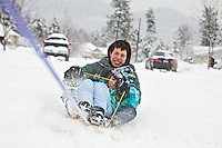 "Evan Puskash, 15, and Faith Nelson, 10, used their snow day away from school to their advantage by ""hookybobbin"" around their Coeur d'Alene neighborhood Friday. They had Jayden Requena, 18, tow them behind her car while they blast through the snow on their sled."