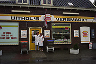 "Cees and Rineke voor hun winkel ""Uithol's Versmarkt"""