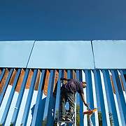 "Manuel Flores, a local Nogales Sonora native joins Artist Ana Teresa Fernández with local and some Arizonians paint the fence in blue color the theme called ""Erasing the Border"" in Nogales Sonora, Mexico on October 13, 2015. Photo by Nick Oza/ The Arizona Republic"