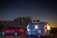 A travel trailer parked at a campsite at Vedauwoo, near Laramie, Wyoming, is illuminated at night with stars overhead.