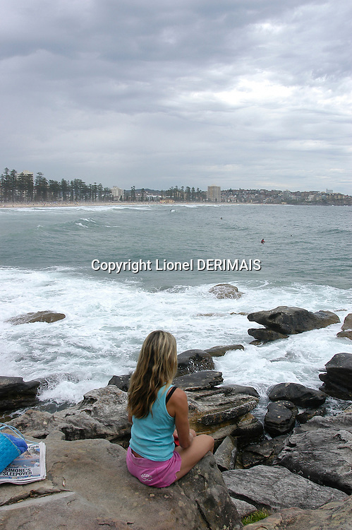 Woman relaxing on the rocks near Manly beach, Sydney, Australia. January 2nd-11th 2007