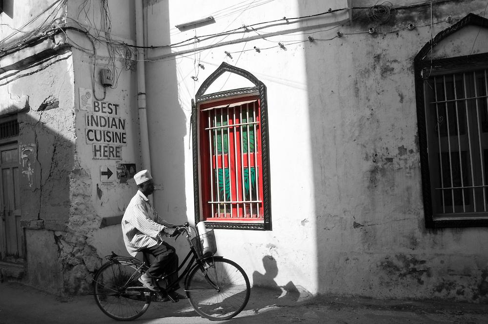 A man riding his bicycle through Stone Town in Zanzibar, Tanzania