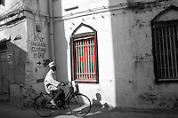 A man riding his bicycle through Stone Town in Zanzibar, Tanzania