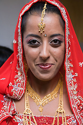 Bride in traditional Asian dress smiling at her wedding,
