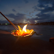 A diyaa, or ceremonial lamp, burns on the shore of the Ganges River during Ganga Aarti in Rishikesh, Uttarakhand, India.