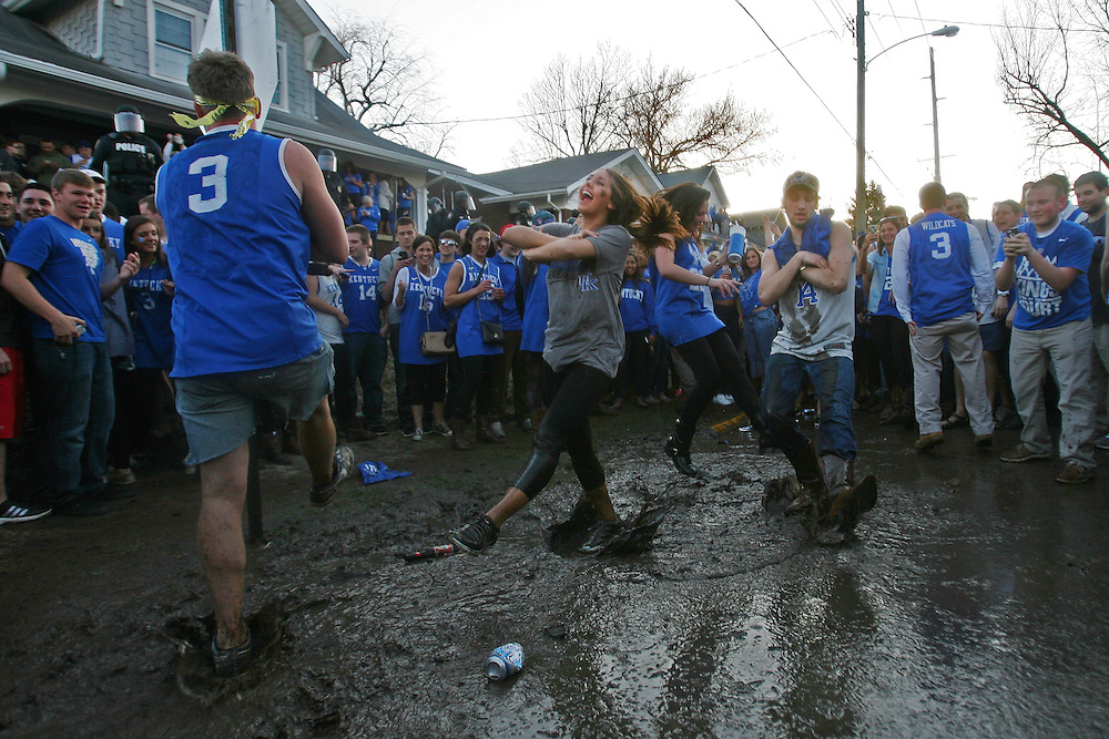 Freshman Maddie Calzi dances in the mud on the corner of State Street and Elizabeth Street in Lexington, Ky., while celebrating Kentucky's last-second win over Michigan that propelled the men's basketball team into the NCAA Final Four.