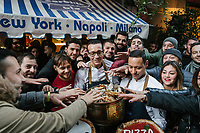 "NAPLES, ITALY - 8 DECEMBER 2017: Gino Sorbillo (39), a Master Pizzaiuolo (pizza chef) and owner of Pizzeria Gino Sorbillo,  together with his brother Toto (right) and a pizzaiuolo (left), are seen here as waiting customers and pedestrians pose for pictures as they reach out to Gino Sorbillo's free pizzas, offered to celebrate the art of Pizzaiuolo added to Unesco's list of Intangible Cultural Heritage of Humanity, here by his pizzeria in Naples, Italy, on December 8th 2017.<br /> <br /> On Thursday December 7th 2017, UNESCO added the art of Neapolitan ""Pizzaiuolo"" to its list of Intangible Cultural Heritage of Humanity.<br /> <br /> The art of the Neapolitan 'Pizzaiuolo' is a culinary practice comprising four different phases relating to the preparation of the dough and its baking in a wood-fired oven, involving a rotatory movement by the baker. The element originates in Naples, the capital of the Campania Region, where about 3,000 Pizzaiuoli now live and perform. Pizzaiuoli are a living link for the communities concerned. There are three primary categories of bearers – the Master Pizzaiuolo, the Pizzaiuolo and the baker – as well as the families in Naples who reproduce the art in their own homes. The element fosters social gatherings and intergenerational exchange, and assumes a character of the spectacular, with the Pizzaiuolo at the centre of their 'bottega' sharing their art.<br /> <br /> In Naples, pizza makers celebrated the victory by giving away free pizzas."