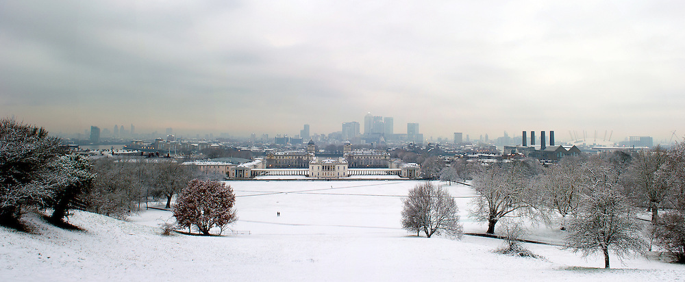 A multi-image composite looking down from the Royal Observatory in Greenwich Park, towards the Maritime Museum, University of Greenwich, across teh River Thames and in the distance the financial district of Canary Wharf.