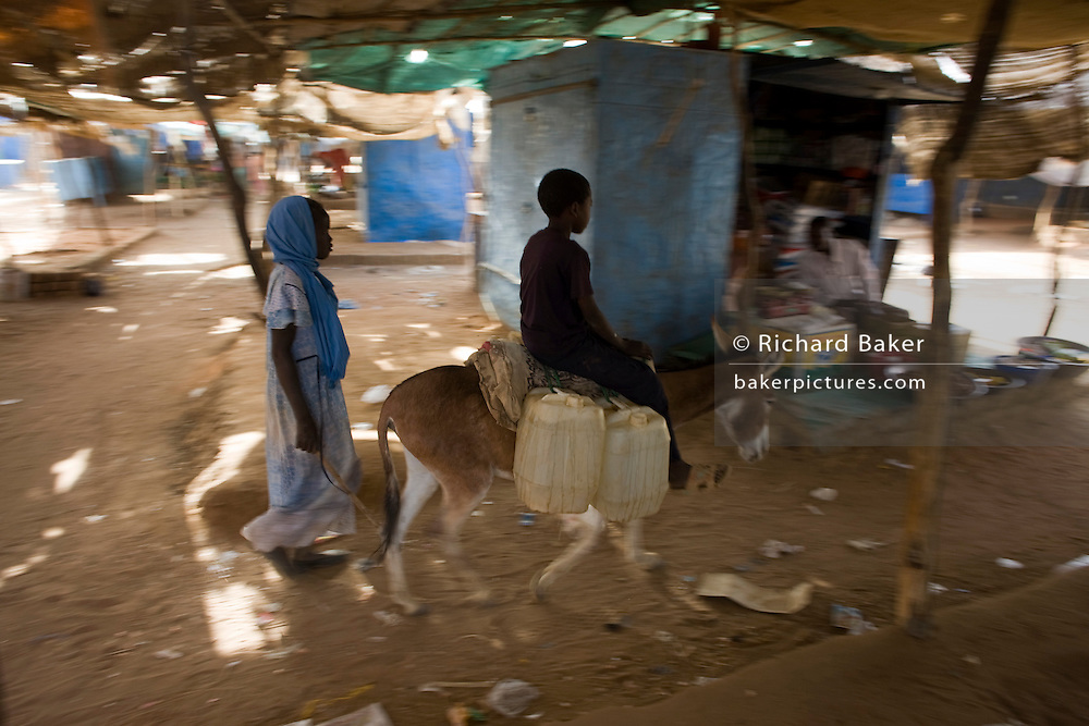 A child rides a mule through the souk market of the 4 sq km Abu Shouk refugee camp which is (disputedly) home to 38,000 displaced persons and families on the outskirts of the front-line town of Al Fasher (also spelled, Al-Fashir) in north Darfur.