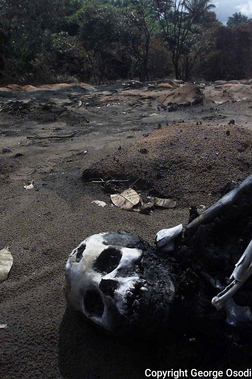 "Charred remains seen on the ground  in Onicha Amiyi-Uhu in Abia state, eastern Nigeria, Sunday, June 22, 2003. Fuel gushing from a vandalized pipeline exploded, killing at least 105 villagers in the rural north eastern Nigeria as they scavenged gasoline. Pipeline vandalism or ""scooping"" is common in Nigeria despite the risk of fire, prosecution or being shot on sight by security forces. (Photo/George Osodi)"