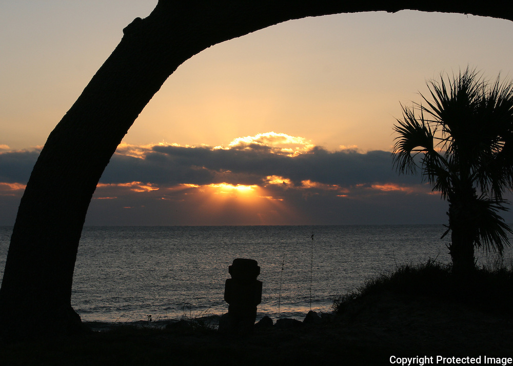 A tiki statue guarding a tropical island beach at sunrise.